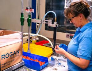 Rogan Corporation Employee Inspecting Part