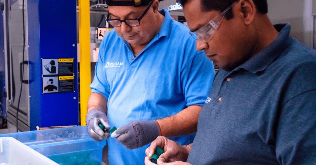 Rogan Employees Inspecting Part